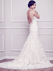 The Mallory gown is an all over lace fit and flare wedding dress with subtle embellishments, spaghetti straps, and a striking low back.