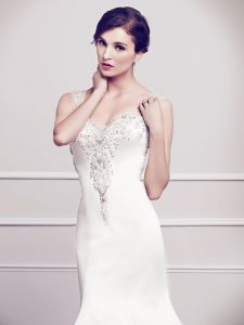 The Angelique wedding gown is pure white with intricate beading and crystal detailing on the straps and neckline.