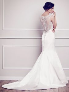 The Angelique gown has an illusion back with intricate, unique lace detailing. The dress is pure white, sleeveless, has round white buttons all the way down the back for a traditional look, and has a trumpet silhouette.