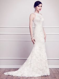 The Talia gown is an all-over lace white wedding gown. It has a sheath silhouette and a high neckline.