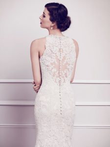 The Talia gown is an all-over lace white wedding gown with a high neck. The back of the gown has round white buttons down the middle for a traditional bridal look.