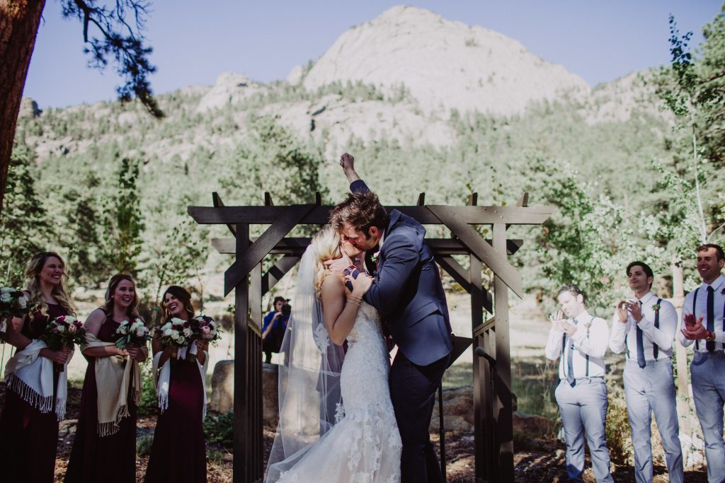 Bride and groom share a kiss after their wedding ceremony as the groom holds his fist in the air in celebration. Jessica and Jeff got married outside in Estes Park, Colorado, with a great view of the Rocky Mountains behind them.