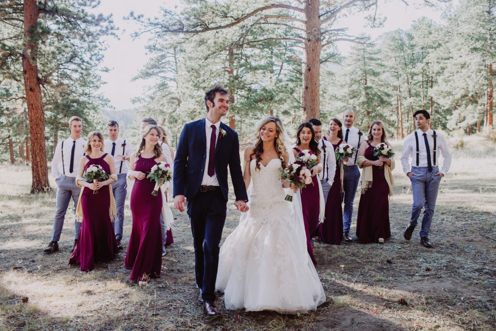 Bride Jessica and her groom Jeff stand outside in the forest of Colorado surrounded by their wedding party members.