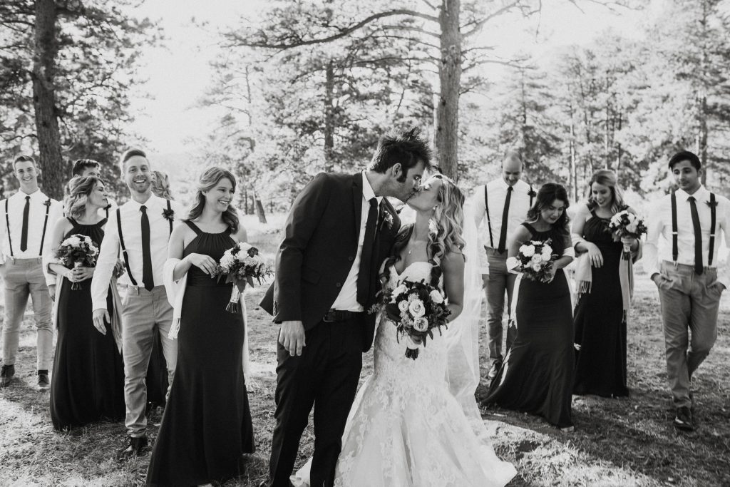 Bridesmaids and groomsmen look on as bride and groom share a kiss.
