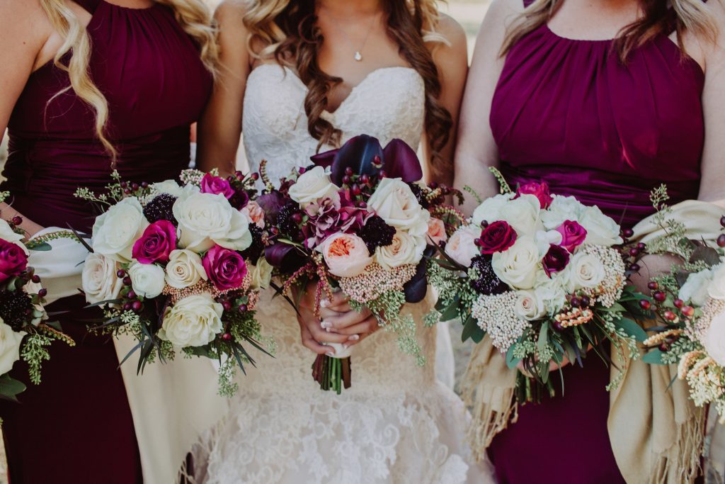 Bride Jessica and her bridesmaids hold out their white, pink, and deep berry-colored wedding bouquets. The bouquets compliment the burgundy color of the bridesmaid dresses.