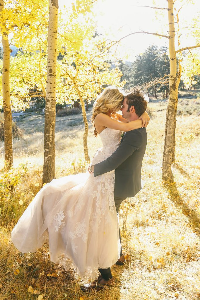 Groom picks up the bride for a romantic, fairytale-like photo amongst the golden aspen leaves at their Colorado autumn wedding in the mountains.