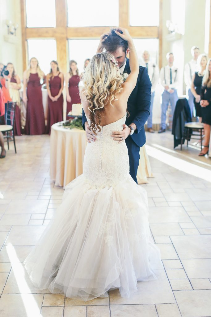 Bride and groom share their first dance as a married couple at their wedding reception as guests watch and smile. The reception took place at Della Terra Mountain Chateau in Estes Park, Colorado.