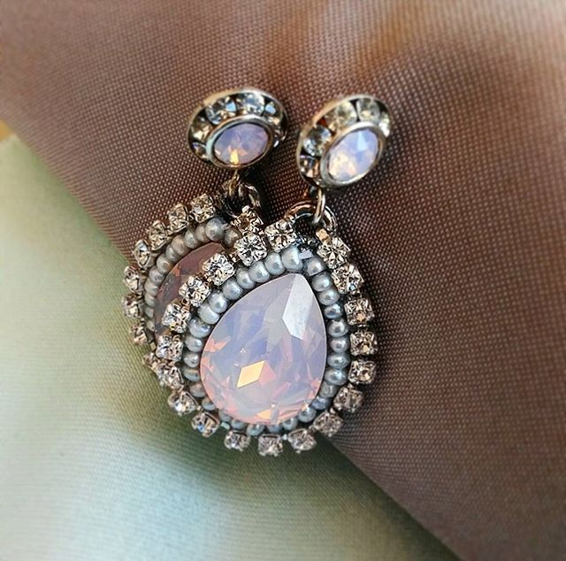 A pair of raindrop shaped bridal earrings with iridescent crystals, beading, and rhinestones.
