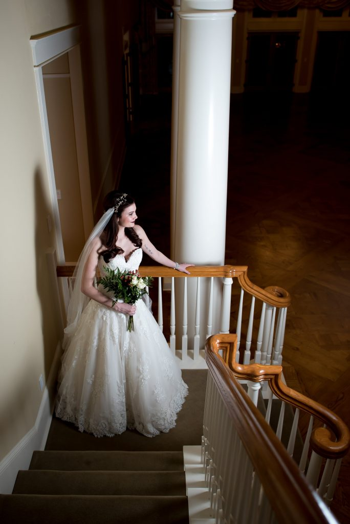 Kelsey stands on the stairs at Flying Horse Ranch in Larkspur, Colorado and models a bridal look featuring a lace ball gown wedding dress with lace and a sweetheart neckline. She holds a winter inspired wedding bouquet and wears a long veil and dark red lipstick. Photo by Moriah Riona, dress by Danelle's Bridal Boutique.