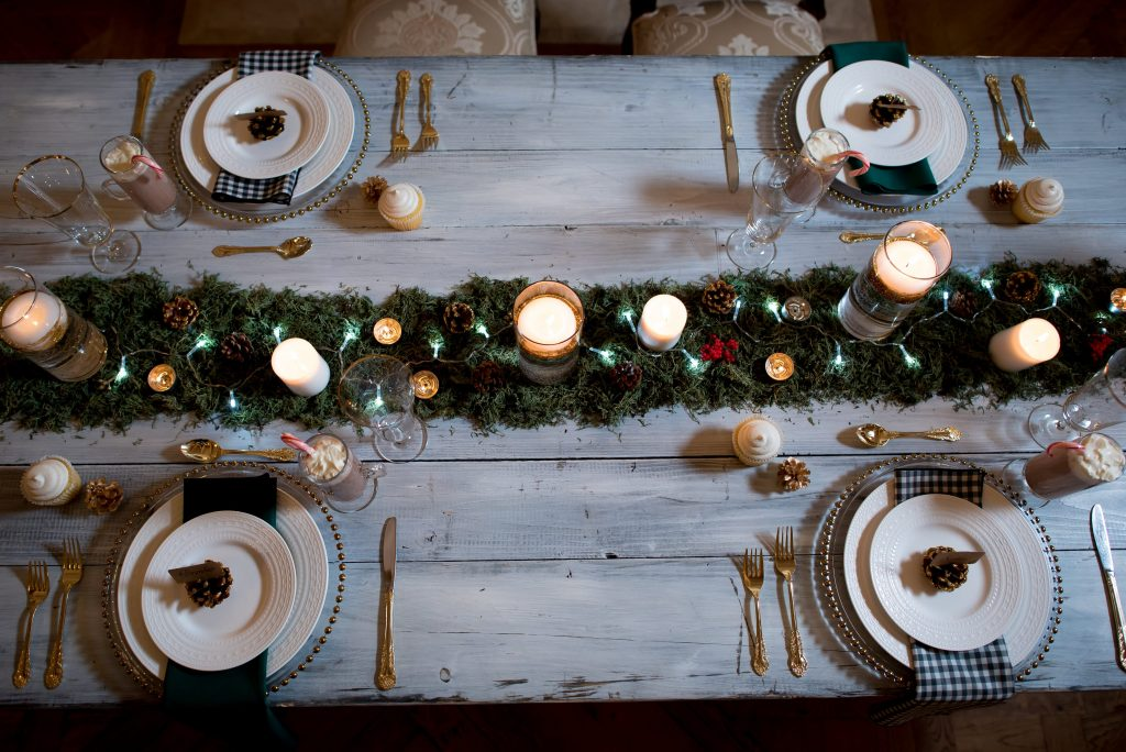 Winter wedding tablescape with lush greenery centerpieces, candles, pinecones, whitewashed wood, and gold cutlery. Photos by Moriah Riona at Flying Horse Ranch in Larkspur, Colorado.
