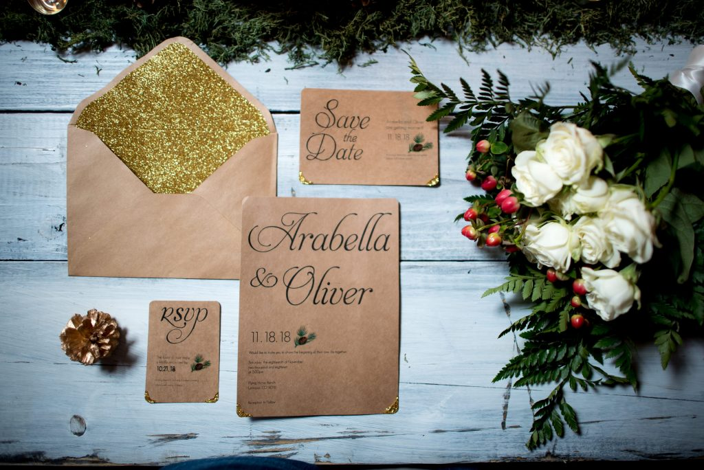 Wedding table setting shows gold glitter and brown paper wedding invitations with script lettering and a red, green, and white wedding bouquet. Photos by Moriah Riona at Flying Horse Ranch in Larkspur, Colorado.