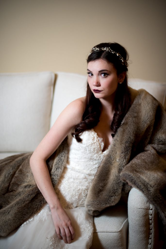 Model shows winter wedding inspired style with dark lipstick, bridal headpiece, faux fur, and an all-over lace sweetheart neckline white wedding gown from Danelle's Bridal Boutique in Colorado Springs. Photos by Moriah Riona at Flying Horse Ranch in Larkspur, Colorado.