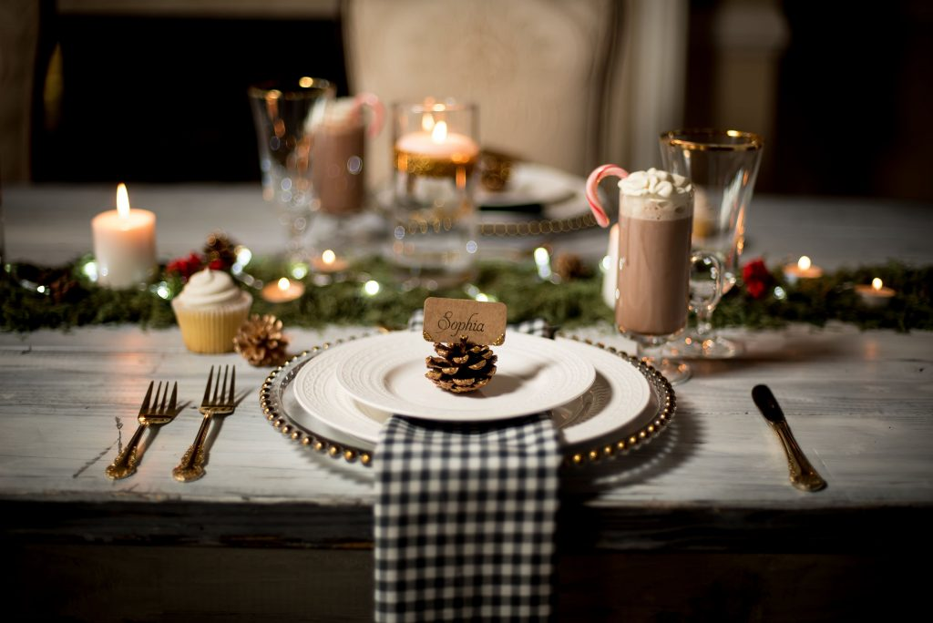 Gold, green, red, black & white winter wedding tablescape with hot cocoa, cupcakes, candles, greenery, gold cutlery & gingham print napkins. Photos by Moriah Riona at Flying Horse Ranch in Larkspur, Colorado.