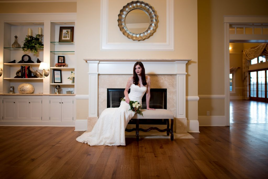 Kelsey models a bridal look featuring a strapless white lace wedding gown from Danelle's Bridal Boutique. She sits in front of a fireplace at Flying Horse Ranch in Larkspur, Colorado for a winter inspired wedding shoot by Moriah Riona.