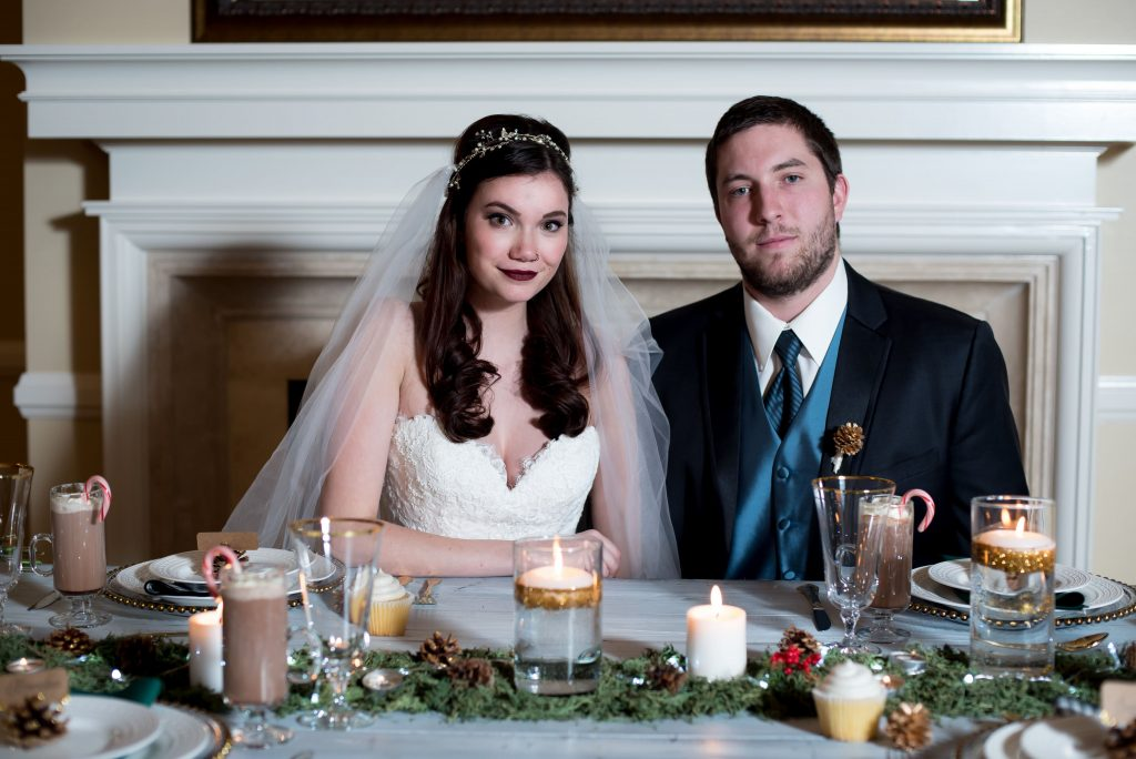 Female model wears a lace sweetheart neckline wedding gown, bridal headpiece, and veil from Danelle's Bridal Boutique. She sits next to the 'groom' who is wearing a tuxedo from Tuxedo Junction. They sit at a winter wedding inspired tablescape with candles, pinecones, hot chocolate, candy canes, candles, and greenery.