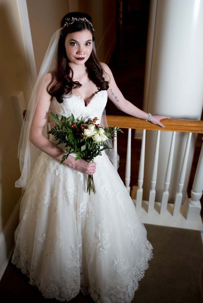 Bride wears dark lipstick, a delicate bridal headpiece, a lace ballgown wedding dress with a sweetheart neckline from Danelle's Bridal Boutique in Colorado Springs. She holds a wedding bouquet that is red, green, and white. Photo by Moriah Riona at Flying Horse Ranch in Larkspur, Colorado.