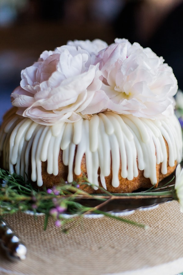 Bundt wedding cake with light pink peonies, wildflowers, and white frosting. Photo by Rachel Havel