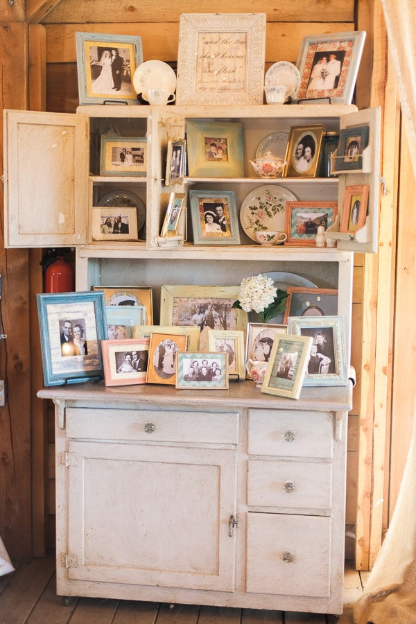 Antique family photos in vintage-inspired chalk painted frames add rustic, old-fashioned charm to a Woodland Park, Colorado wedding. Photo by Rachel Havel