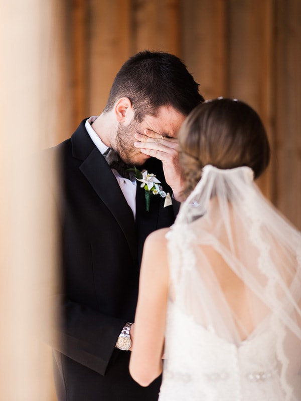 A groom wipes away tears as he sees his bride for the first time at their wedding in Woodland Park, Colorado. Photo by Rachel Havel