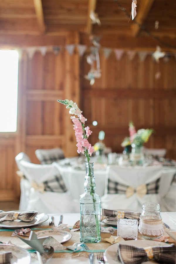 DIY table setting at a whimsical vintage wedding inside a rustic barn in Woodland Park, Colorado. Photo by Rachel Havel