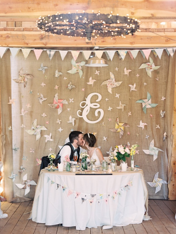 A bride and groom sit in front of a handmade DIY backdrop at their rustic Colorado wedding. The backdrop is made with handmade pennant banners and pinwheels, and has a script monogram letter for the couple's last name. Photo by Rachel Havel