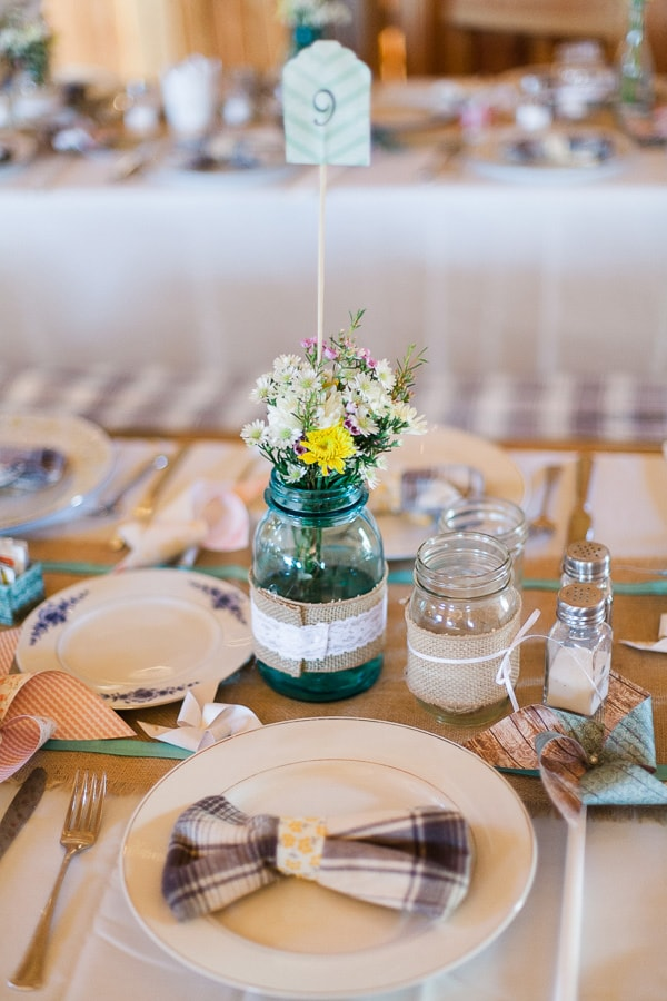 Mason jars decorated in burlap and lace are used as vases for wildflowers at a rustic Colorado wedding table setting. All the decor was handmade. Photos by Rachel Havel