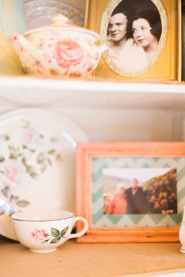 Floral teacups and plates sit next to old family photos inside hand painted picture frames inside an antique cupboard. This decor was used for a whimsical wedding in Woodland Park, Colorado. Photo by Rachel Havel