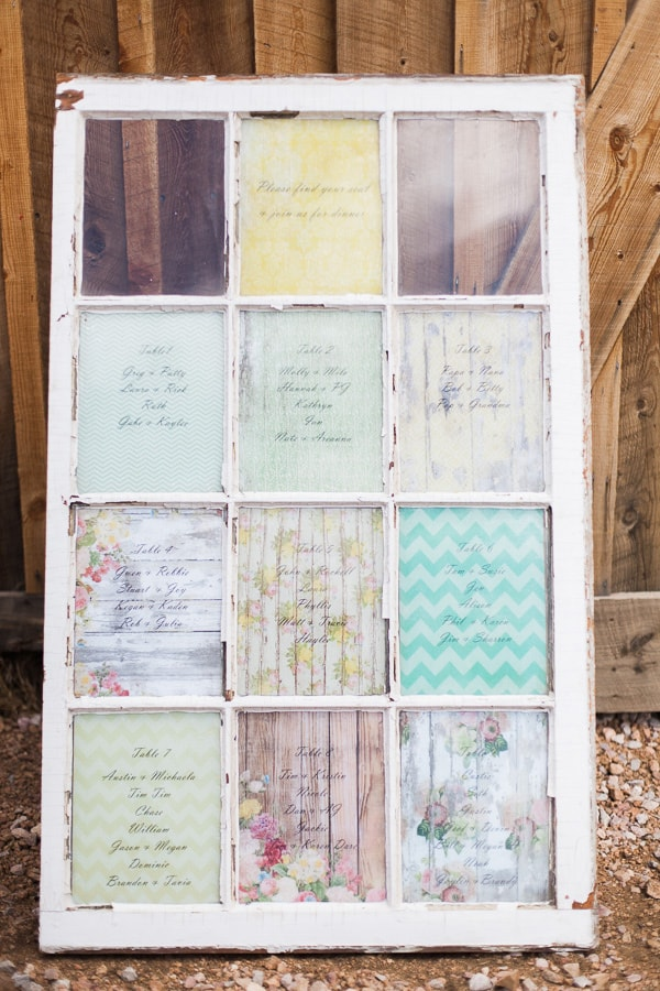 Old window used as a seating chart for a rustic Woodland Park, Colorado wedding. Each window panel has script lettering and patterned paper for a whimsical, vintage look. Photo by Rachel Havel