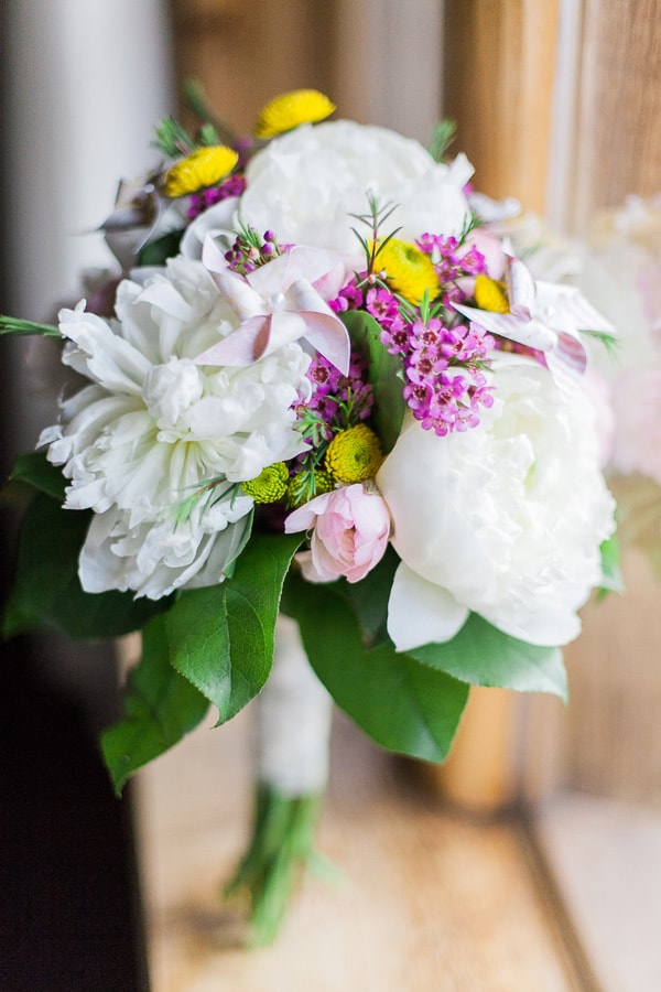 Rustic vintage wedding bouquet with handmade pinwheels, white peonies, and raunculus for a ceremony in Woodland Park, Colorado. Photo by Rachel Havel