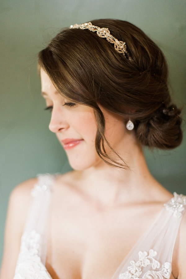 A bride wears a low bun wedding hairstyle with an embellished gold bridal headband. She wears a white wedding gown from Danelle's Bridal Boutique and natural makeup. Photo by Rachel Havel