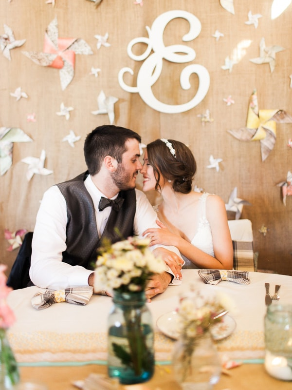 A bride and groom sit in front of a vintage-inspired DIY backdrop at their Woodland Park, Colorado wedding reception. Photo by Rachel Havel