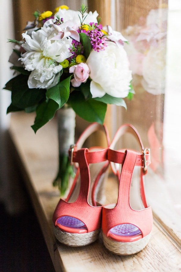 A colorful bridal bouquet and bright red wedge heels sit on a windowsill before Rachel & Chris' wedding in Woodland Park, Colorado.