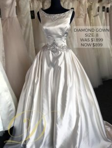 Diamond Wedding Gown Size 8 at Danelle's Bridal Outlet in Pueblo, Colorado. Original price $1,899 now just $899 outlet sale price. Satin ballgown with embellishments at waist and bateau neckline.
