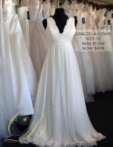 Graciela Wedding Gown size 10 at Danelle's Bridal Outlet in Pueblo, Colorado. A breezy white bridal gown in chiffon with lace detailing at the waistline and neckline. Now only $899 marked down from original price of $1,549.