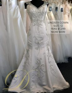 Lindsey Wedding Gown at Danelle's Bridal Outlet in Pueblo, Colorado. Size 12 satin wedding gown with embellishments throughout. Now $699 marked down from $1,299.