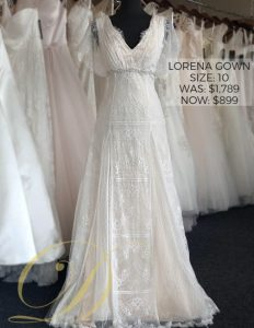 Lorena Wedding Dress at Danelle's Bridal Outlet in Pueblo, Colorado. A delicate lace vintage style fit and flare bridal gown with flutter sleeves and empire waist bridal belt attached. Now on sale for $899, marked down from $1,789.