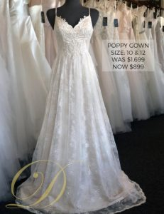 Poppy Wedding Gown at Danelle's Bridal Outlet in Pueblo, Colorado. Sizes 10 & 12 available. A boho lace spaghetti strap wedding dress with layers of lace and embroidered bodice. Shown in champagne color.